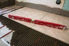 Keramische tegels en hulpmiddelen voor tegelzetter De installatie van vloertegels Hom stock fotografie