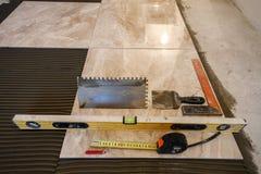Keramische tegels en hulpmiddelen voor tegelzetter De installatie van vloertegels Hom Stock Foto's