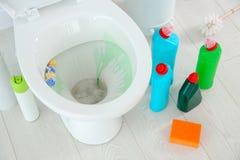 Keramische Toilettenschüssel, Flaschen des Reinigungsmittels Stockfotografie