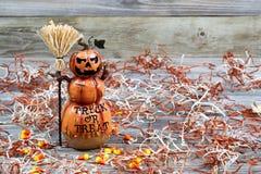 Keramische Zahl des furchtsamen großen orange Kürbises auf rustikalem Holz Stockfoto