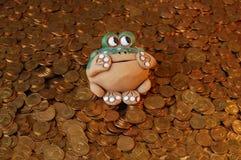 Keramischer Frosch auf einer großen Vielfalt von Münzen Lizenzfreies Stockbild