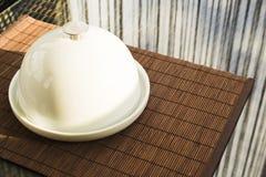 Keramischer Präsentierteller mit weißem Teller über Glastisch stockbild