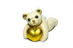 Keramischer Teddybär, der ein Herz umarmt stockfotografie