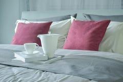 Keramischer Teesatz und -bücher, die auf Bett mit rotem Samt einstellen, pillows zu Hause lizenzfreie stockfotografie