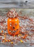 Keramisches Glas des furchtsamen großen orange Kürbises auf rustikalem Holz Stockbilder
