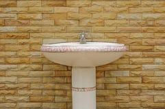 Keramisches weißes Waschbecken mit einem Hahn auf Ziegelsteinhintergrund Lizenzfreie Stockbilder