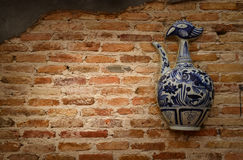 Keramisk flaska på den gamla väggen royaltyfria bilder