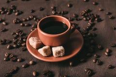 Keramisk kaffekopp med farinkuber och spridda kaffekorn Arkivfoto