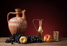 Keramisk kanna och nya druvor Arkivbild