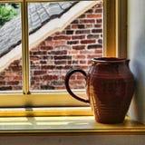 Keramisk kanna på fönsterbräda Arkivfoto