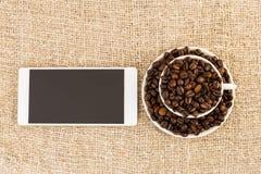 Keramisk kopp kaffebönor och smartphone Arkivfoto