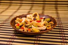 Keramisk platta med olika havsmat och oliv på en matt bambu Royaltyfria Bilder