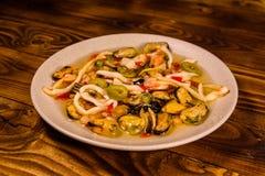 Keramisk platta med olika havsmat och oliv på trätabellen Royaltyfria Foton