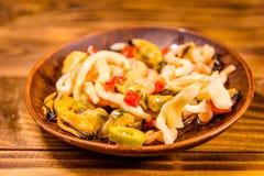 Keramisk platta med olika havsmat och oliv på trätabellen Royaltyfri Foto