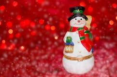 Keramisk snögubbe på röd bokehbakgrund Royaltyfria Foton