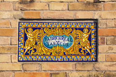 Keramisk tegelplatta av den kungliga tobakfabriken i Seville, Spanien arkivfoton
