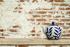 Keramisk tekanna med gammal bakgrund för tappningtegelstenvägg Fotografering för Bildbyråer