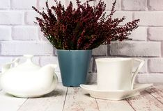 Keramisk vit kopp och tekanna för tappning på vit träbakgrund med ljung, kopieringsutrymme royaltyfri foto