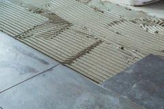 Keramiska golvtegelplattor som läggas på applicerat bindemedel fotografering för bildbyråer