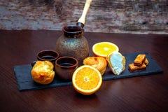 Keramiska koppar, kaffe som bryggar krukan, apelsin, profiterole eller eclairkakor och godisar arkivbilder