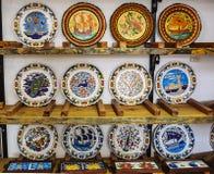 Keramiska souvenirplattor på utställningen och försäljningen i ett modernt krukmakeriseminarium royaltyfria bilder
