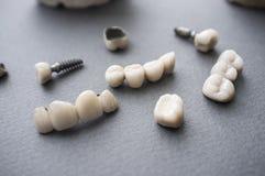 Keramiska tandproteser och kronor på grå bakgrund Arkivbild