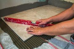 Keramiska tegelplattor och hjälpmedel för tiler Arbetarhand som installerar golvet Royaltyfria Foton
