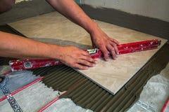 Keramiska tegelplattor och hjälpmedel för tiler Arbetarhand som installerar golvet Arkivbild