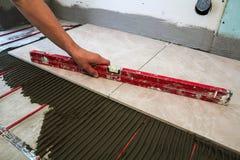 Keramiska tegelplattor och hjälpmedel för tiler Arbetarhand som installerar golvet Royaltyfria Bilder