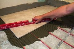 Keramiska tegelplattor och hjälpmedel för tiler Arbetarhand som installerar golvet Royaltyfri Foto