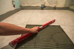 Keramiska tegelplattor och hjälpmedel för tiler Arbetarhand som installerar golvtegelplattor Hemförbättring renovering - bindemed Arkivbild