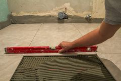 Keramiska tegelplattor och hjälpmedel för tiler Arbetarhand som installerar golvtegelplattor Hemförbättring renovering - bindemed Royaltyfri Bild
