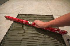 Keramiska tegelplattor och hjälpmedel för tiler Arbetarhand som installerar golvtegelplattor Hemförbättring renovering - bindemed Royaltyfria Foton