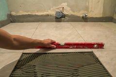 Keramiska tegelplattor och hjälpmedel för tiler Arbetarhand som installerar golvtegelplattor Hemförbättring renovering - bindemed Royaltyfri Foto