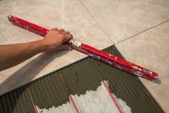 Keramiska tegelplattor och hjälpmedel för tiler Arbetarhand som installerar golvtegelplattor Hemförbättring renovering - bindemed Arkivbilder