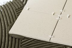 Keramiska tegelplattor och hjälpmedel för tiler Installation för golvtegelplattor Hemförbättring renovering - bindemedel för golv Royaltyfri Bild