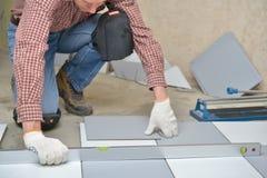 keramiskt golv som installerar tegelplattor royaltyfri bild