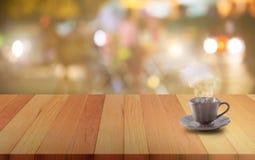Keramiskt kaffe rånar på ett träbräde eller bordlägger och gör sammandrag blurr Arkivbild