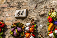 Keramiskt nummer sextiofyra 64 på en tegelstenvägg royaltyfri fotografi