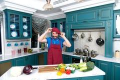 Kerel bij keuken het kleden zich schort en hoed De chef-kok draagt rode eenvormig De mens kleedde zich op rode hoed op hand stock fotografie