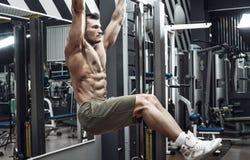 Kerel bodybuilder do chin-ups stock afbeeldingen