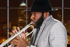 Kerel in de trompet van hoedenspelen Royalty-vrije Stock Fotografie