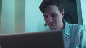 Kerel die de zitting van de notitieboekjecomputer gebruiken dichtbij venster stock videobeelden