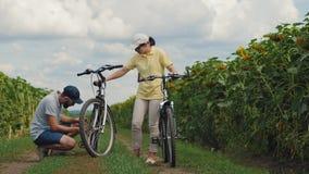 Kerel die een fiets herstellen zijn meisje stock footage