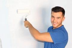 Kerel die een geïsoleerde muur schilderen Stock Foto