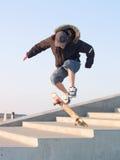 Kerel die een stunt met zijn skateboard doet Royalty-vrije Stock Fotografie