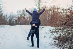 Kerel die en zijn meisje houden de opheffen dient de winter binnen bosmeisje in die wapens opheffen Mensen die pret hebben in ope royalty-vrije stock fotografie