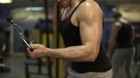 Kerel die hard in gymnastiek werken die levendige pull-downs met één wapen doen, beëindigend oefening stock footage