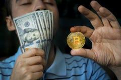 Kerel die het muntstuk bitcoin en in hand geld houden Royalty-vrije Stock Afbeeldingen