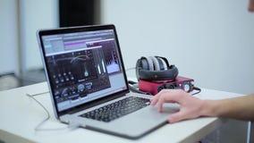 Kerel die met muzieksoftware aan laptop werken stock videobeelden